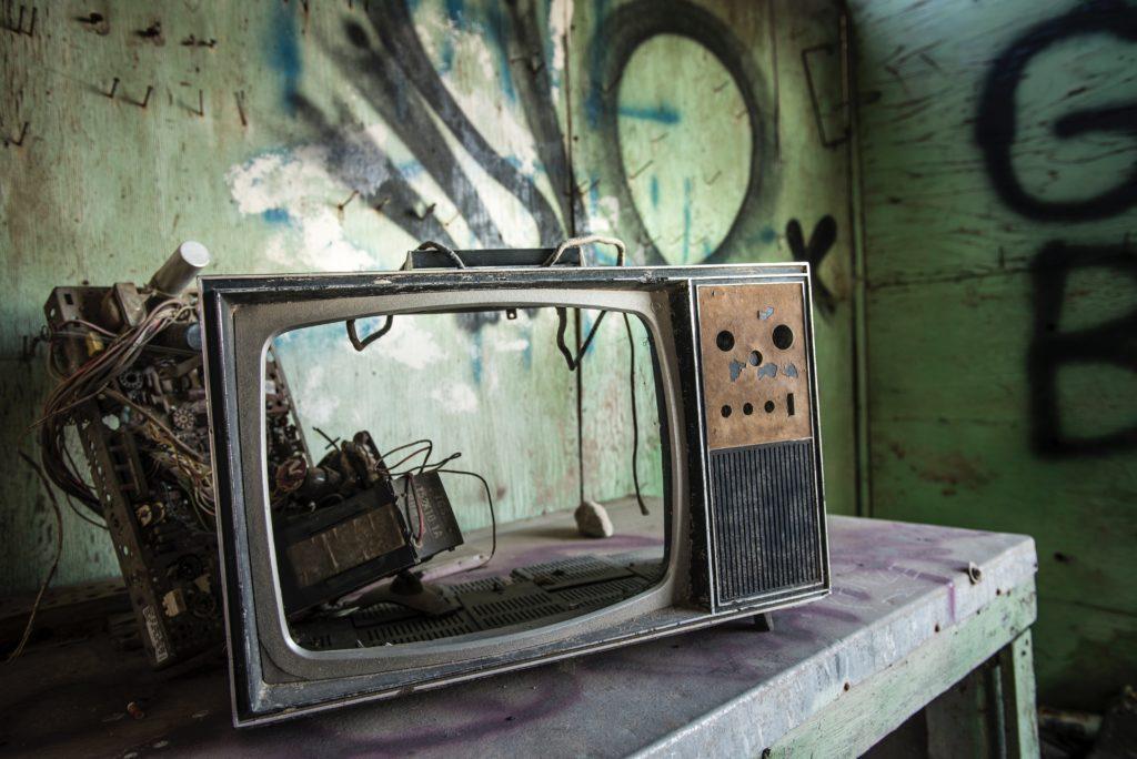 A imagem mostra um televisor desmontado junto com a parte elétrica, numa mesa de madeira. Fundo esverdeado